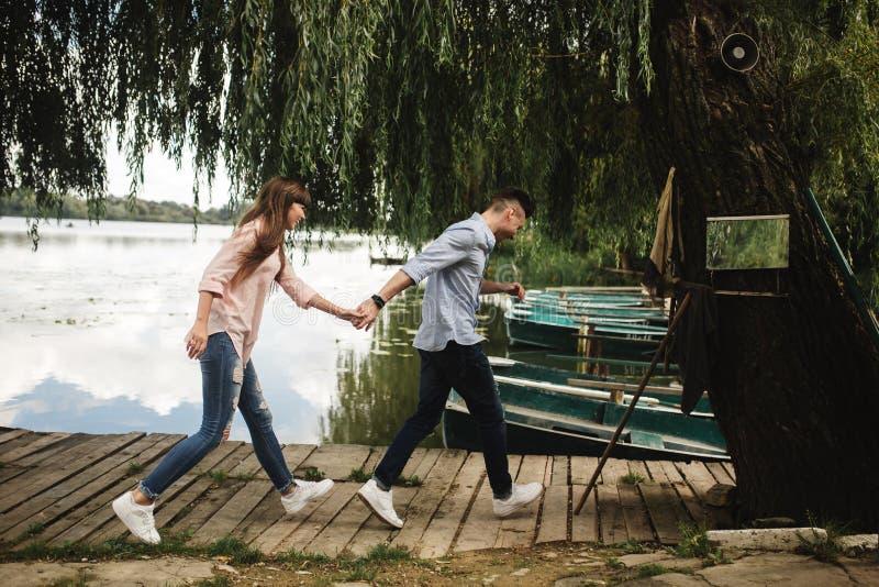 Gelukkig jong paar in openlucht jong liefdepaar die langs handen van een de houten brugholding lopen royalty-vrije stock foto