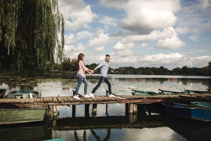 Gelukkig jong paar in openlucht jong liefdepaar die langs handen van een de houten brugholding lopen royalty-vrije stock afbeelding
