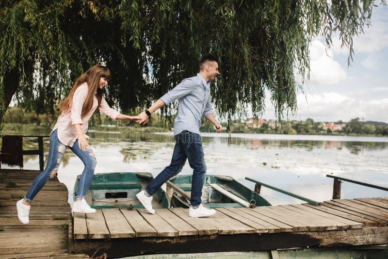 Gelukkig jong paar in openlucht jong liefdepaar die langs handen van een de houten brugholding lopen stock foto's