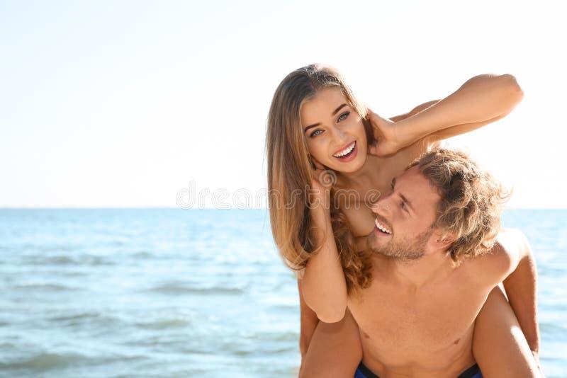Gelukkig jong paar in strandkleding die pret samen op kust hebben royalty-vrije stock afbeelding