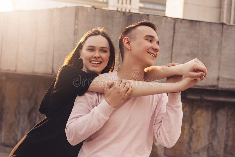 Gelukkig jong paar van vrienden, tieners die, studenten bij stadsstraat koesteren royalty-vrije stock foto's