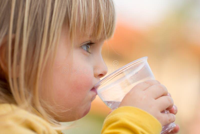 Gelukkig jong van het de mensenmeisje van het baby Kaukasisch blonde echt dicht openlucht het portret drinkwater stock foto's