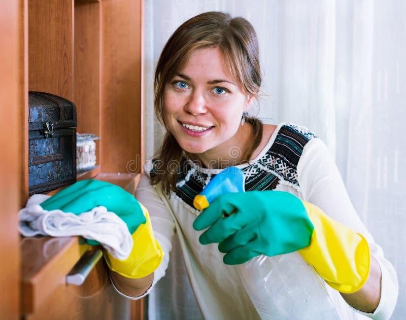 Gelukkig jong volwassen brunette die met reinigingsmiddel bestrooien royalty-vrije stock foto's