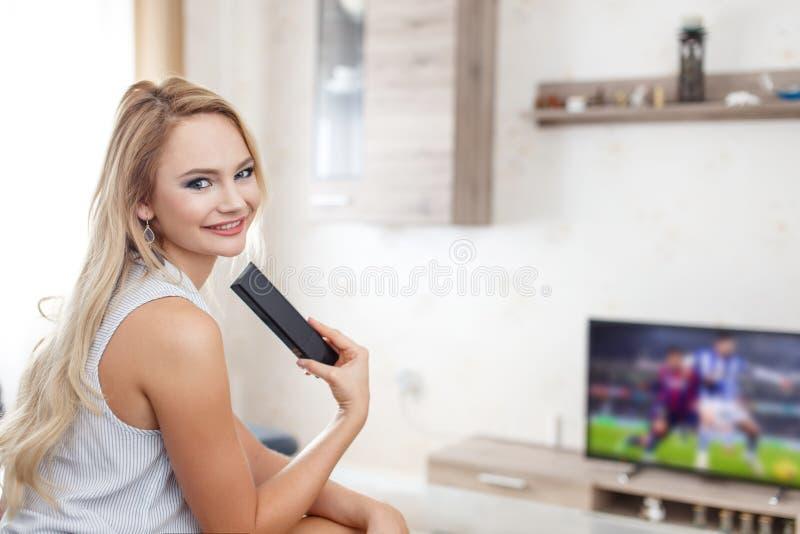 Gelukkig jong vrouw het letten op voetbal in TV stock afbeelding