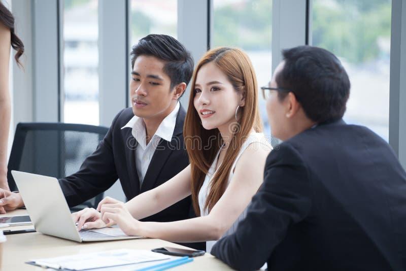 gelukkig jong zakenman en onderneemsterteam die samen met laptop computer aan bureau werken die informatie in bureau bespreken We stock afbeeldingen