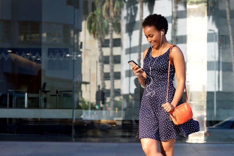Gelukkig jong zwarte dat mobiele telefoon bekijkt en aan muziek luistert stock afbeeldingen