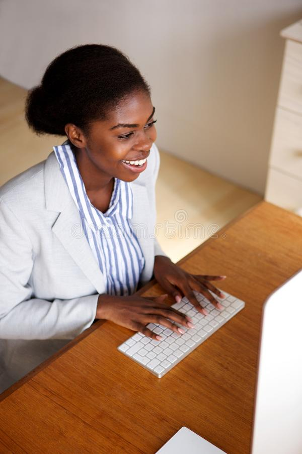 Gelukkig jong zwarte die met computer in bureau werken royalty-vrije stock fotografie