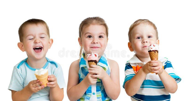 Gelukkig jonge geitjesjongens en meisje die geïsoleerdd roomijs eten stock fotografie