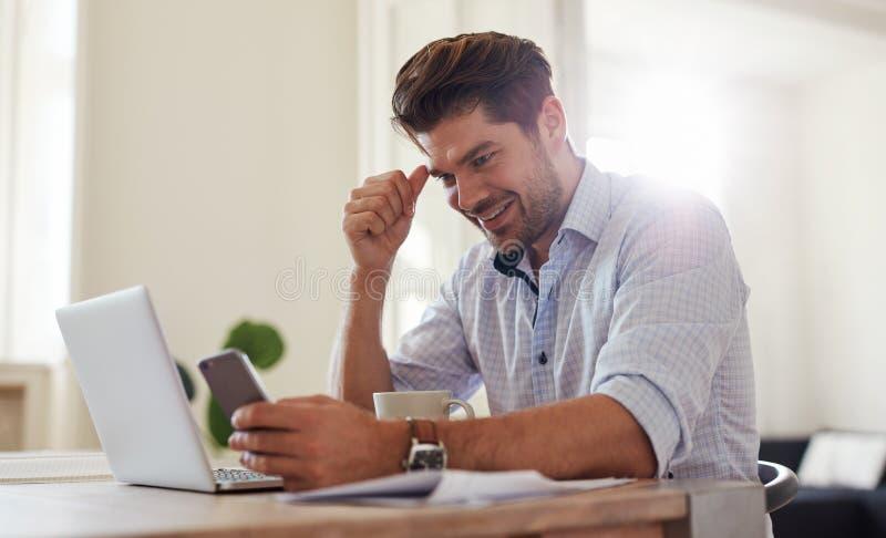 Gelukkig jonge mensen thuis bureau die mobiele telefoon met behulp van royalty-vrije stock fotografie