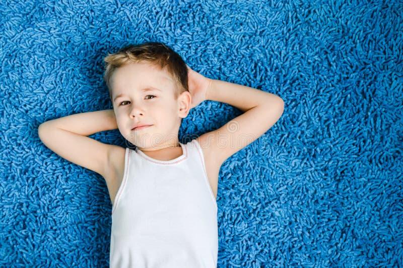 Gelukkig jongen het glimlachen jong geitje die camera op blauw tapijt in woonkamer thuis bekijken stock foto