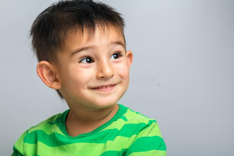 Gelukkig jongensgezicht, portret van een kind op een grijze achtergrond stock fotografie