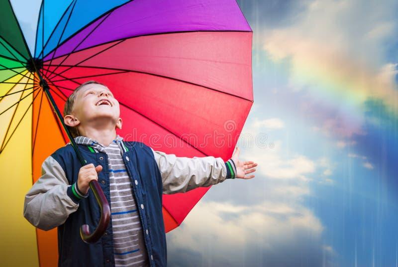 Gelukkig jongensportret met heldere regenboogparaplu royalty-vrije stock fotografie