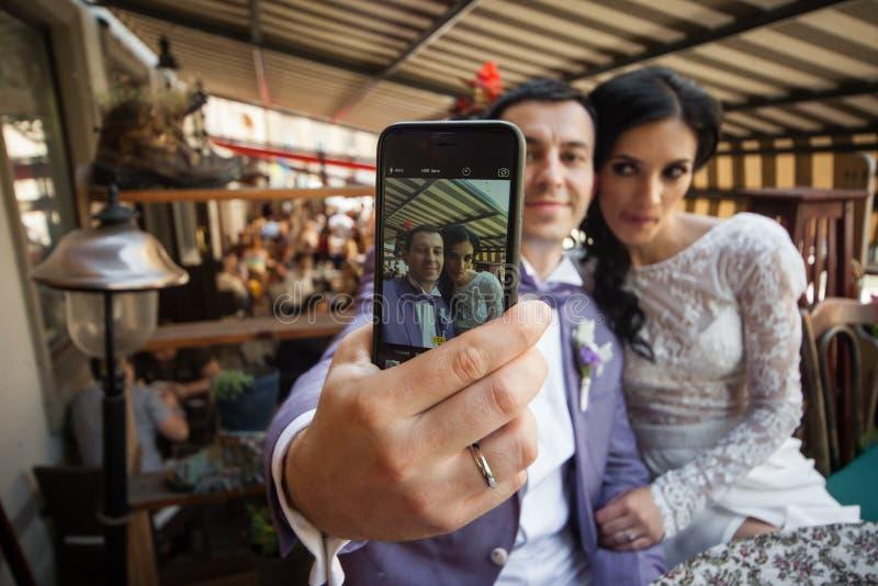 Gelukkig jonggehuwdepaar die een selfie op hun telefoon nemen stock fotografie
