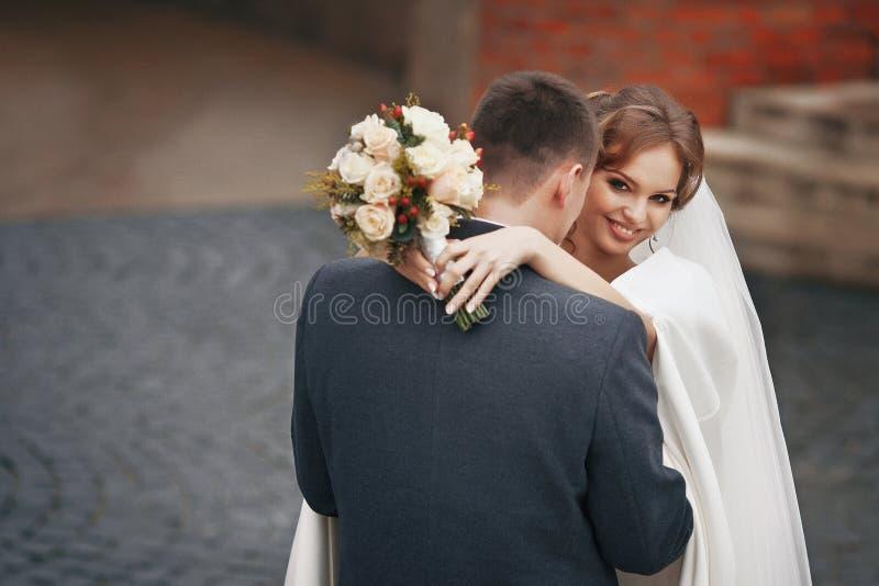 Gelukkig jonggehuwdepaar die met boeket in openlucht koesteren royalty-vrije stock foto's