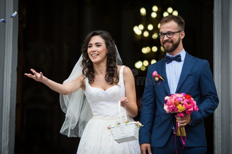 Gelukkig jonggehuwdepaar die uit kerk komen, die boeket houden en stock foto