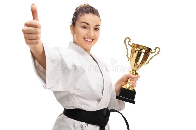 Gelukkig karatemeisje die duim opgeven en gouden trofee houden stock afbeelding