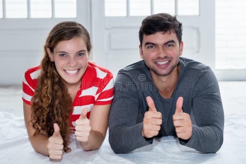Gelukkig Kaukasisch liefdepaar die camera in nieuwe flat bekijken stock foto's
