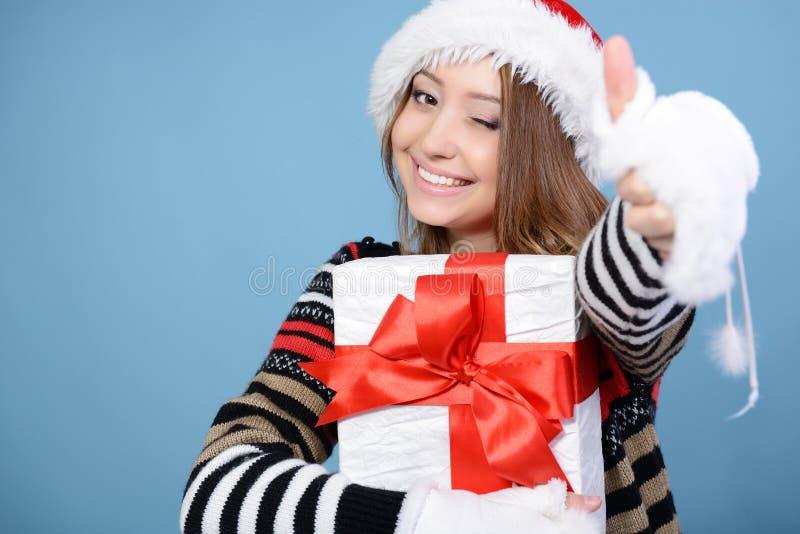 Gelukkig Kerstmismeisje met omhoog duim, jonge mooie vrouw die en huidige dozen over wit glimlachen houden royalty-vrije stock afbeeldingen