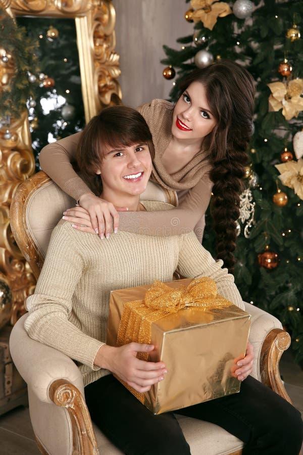 Gelukkig Kerstmispaar in liefde Jong donkerbruin meisje die hand koesteren royalty-vrije stock afbeelding