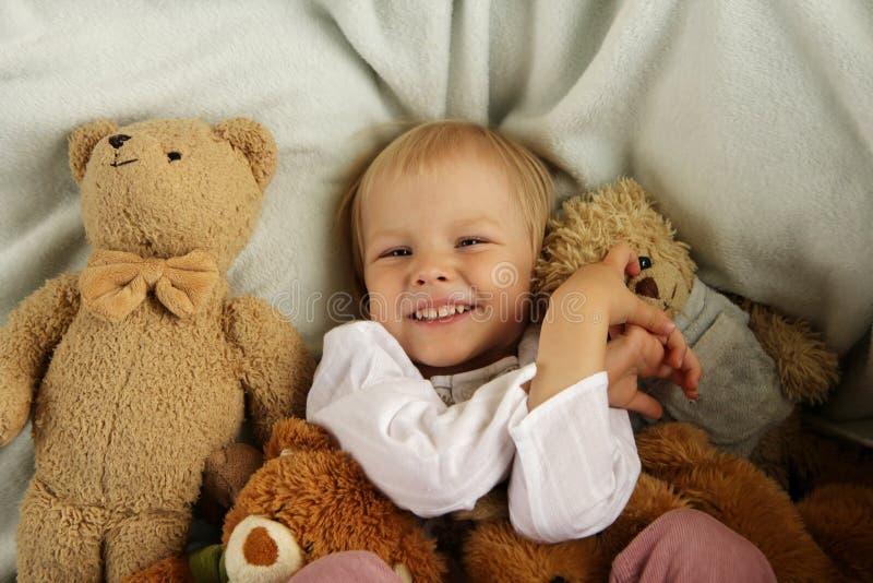 Gelukkig kind in bed met teddybeer royalty-vrije stock afbeelding