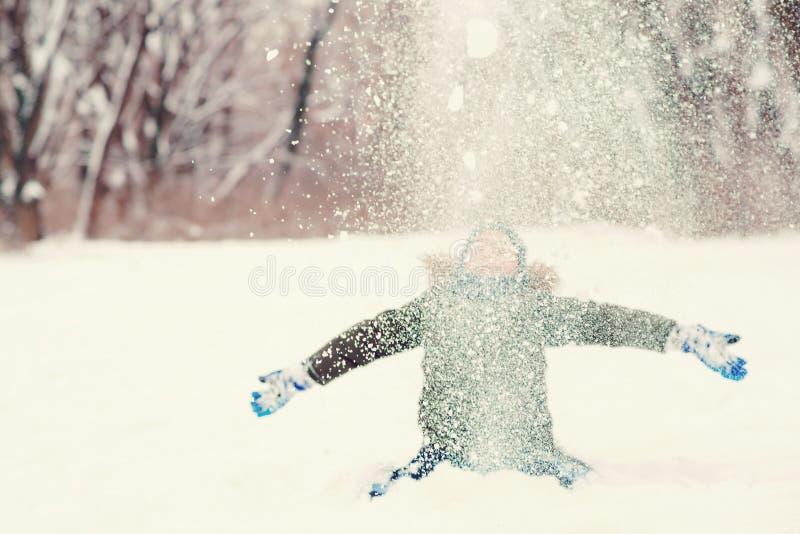 Gelukkig kind dat plezier heeft in de sneeuw Cute boy gooit sneeuw, geniet van sneeuwweersomstandigheden Fijne winter en kerstvak stock afbeelding