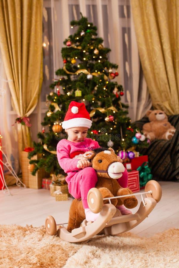 Gelukkig kind dat thuis plezier heeft in de kerstavond stock fotografie