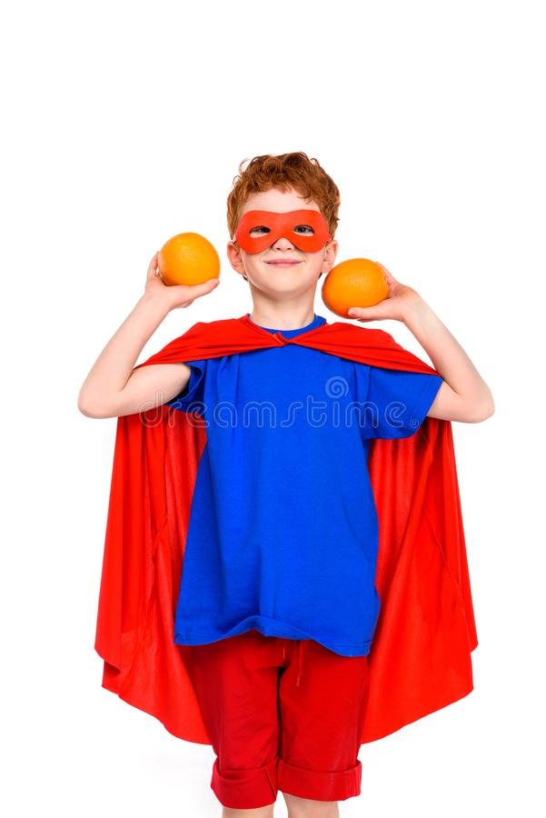 gelukkig kind in de holdingssinaasappelen van het superherokostuum en het glimlachen bij camera stock fotografie