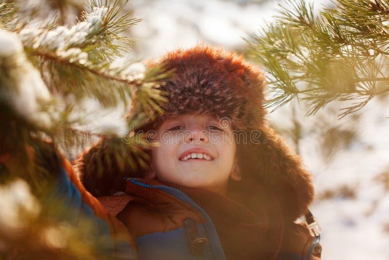 Gelukkig kind die in een de winterbos lopen in zonnige dag stock afbeeldingen