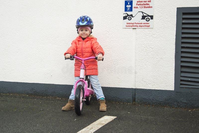 Gelukkig kind die een fiets in de herfst berijden Leuk meisje in veiligheidshelm die een fiets in openlucht berijden Meisje op ee royalty-vrije stock afbeeldingen