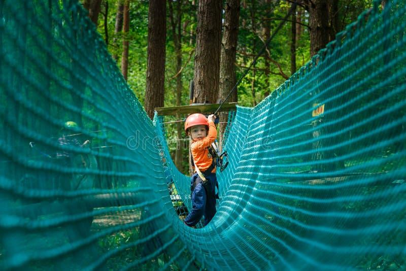Gelukkig kind die in een het beklimmen avonturenpark genieten van stock foto