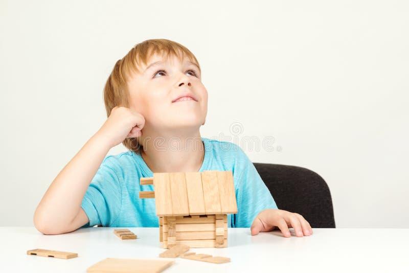 Gelukkig kind die en houten huis spelen bouwen Kinderjarendromen Weinig jongen bouwt zijn droomhuis Het gelukkige leven, huis of  stock afbeeldingen