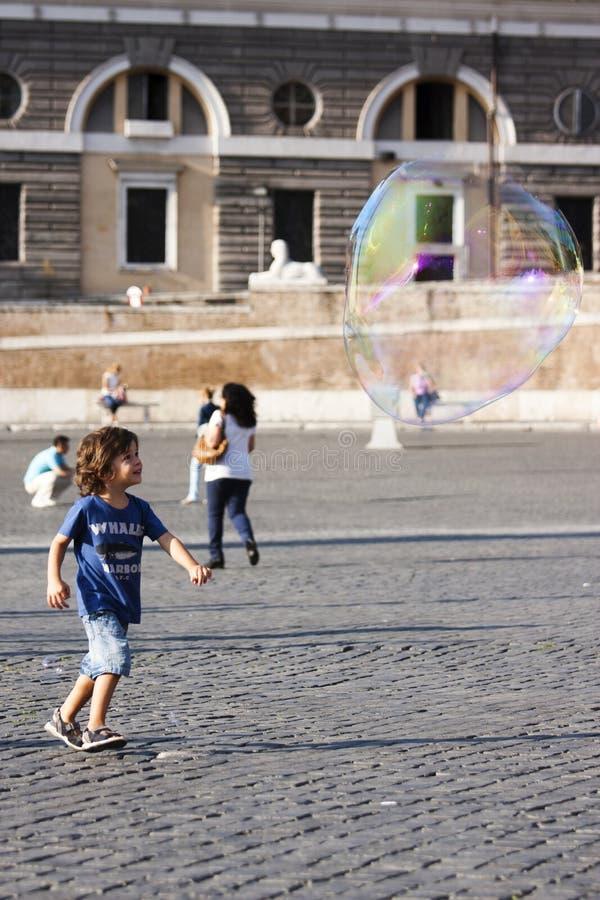 Gelukkig kind die naar een zeepbel lopen stock afbeelding