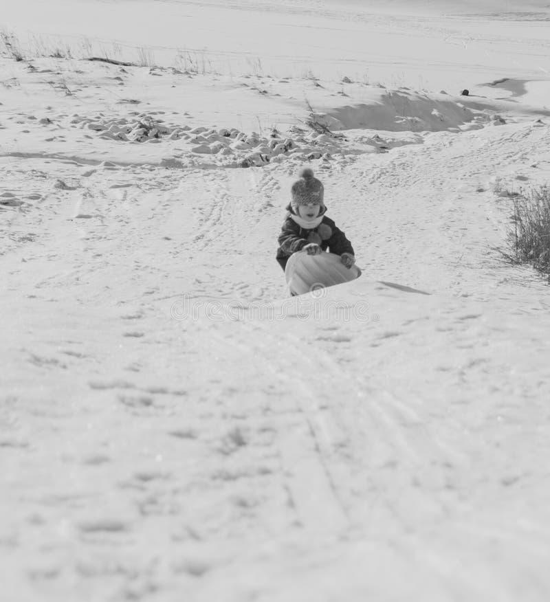 Gelukkig kind die op een sneeuwheuvel in de winter berijden stock fotografie
