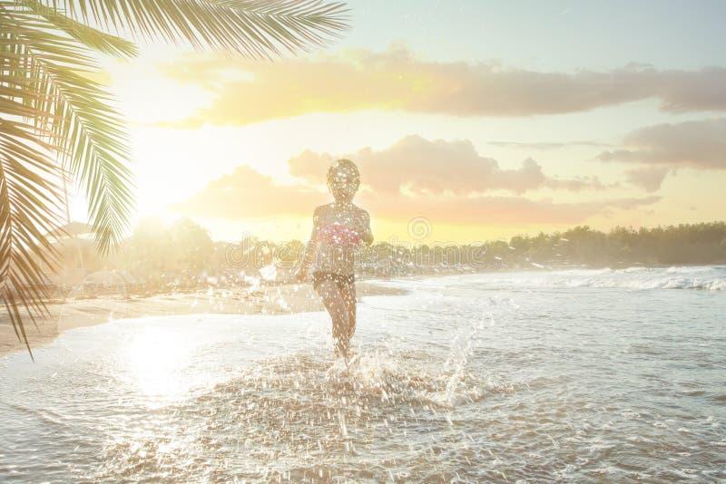 Gelukkig kind die op overzees strand lopen en van zeewater en zon genieten royalty-vrije stock foto