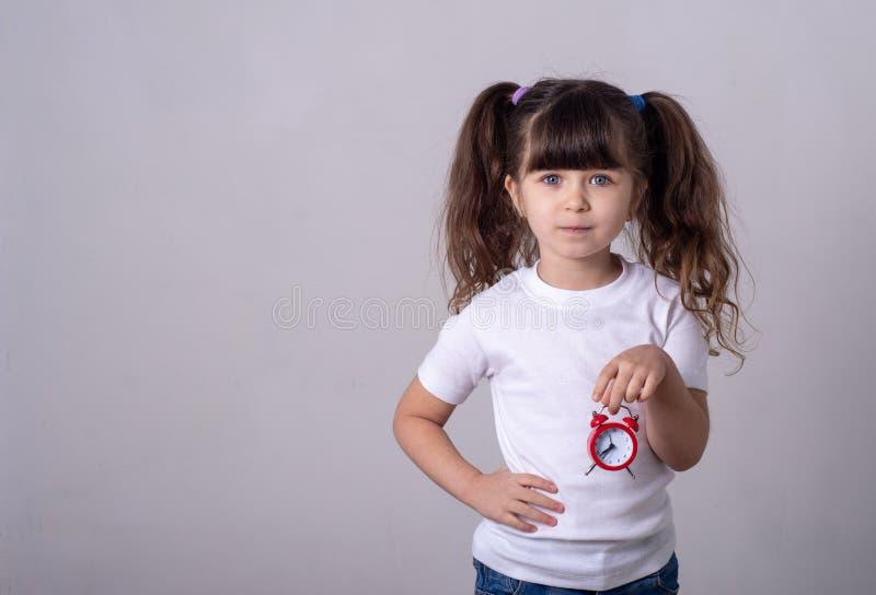 Gelukkig kind die rode klok op grijze achtergrond houden Jong geitje met Wekker stock foto