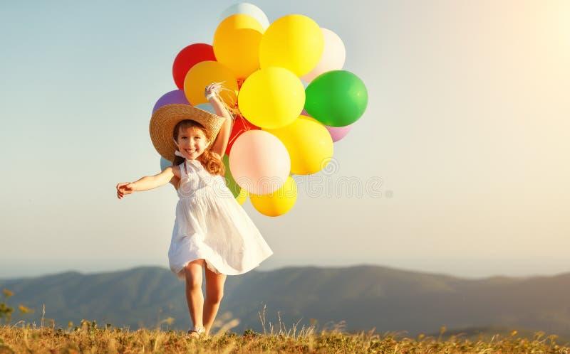 Gelukkig kind met ballons bij zonsondergang in de zomer stock foto