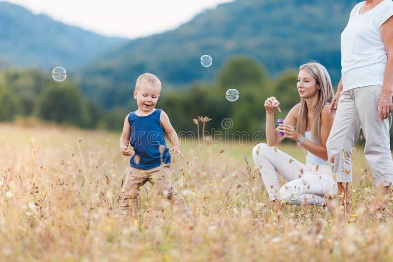 Gelukkig kind met familie die een grote tijd blazende bellen hebben stock afbeelding