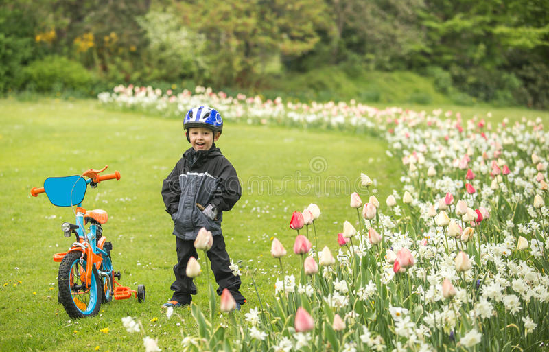 Gelukkig kind met fiets in park stock foto