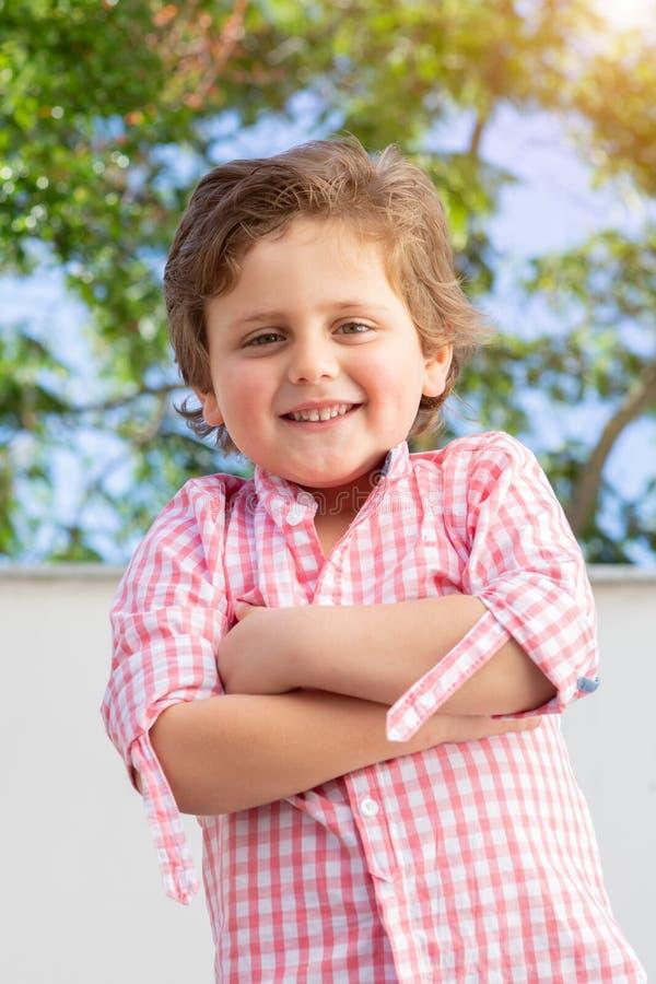 Gelukkig kind met roze overhemd in de tuin stock foto's