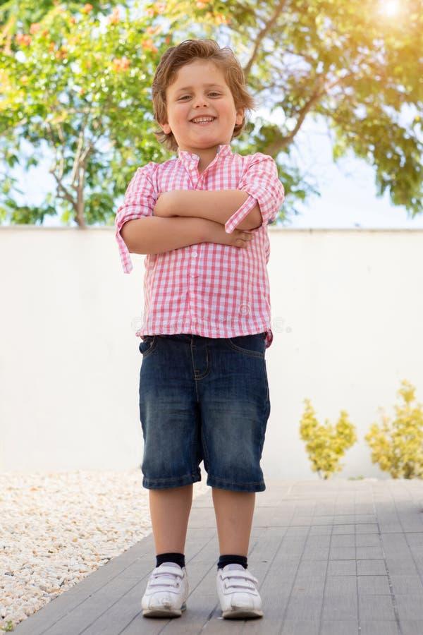 Gelukkig kind met roze overhemd in de tuin royalty-vrije stock afbeeldingen