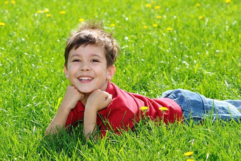 Gelukkig kind op groen gras stock afbeeldingen