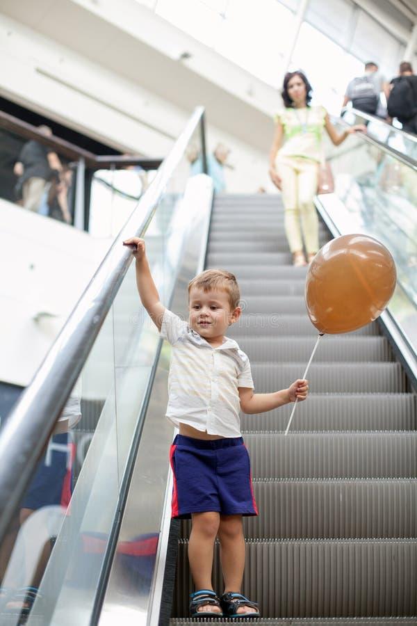 Gelukkig kind op roltrap in winkelcentrum Weinig jongen die bruine ballon houden stock foto