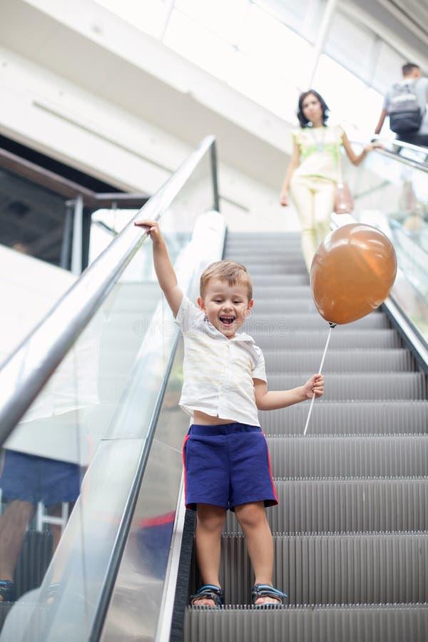 Gelukkig kind op roltrap in winkelcentrum Weinig jongen die bruine ballon houden royalty-vrije stock afbeeldingen