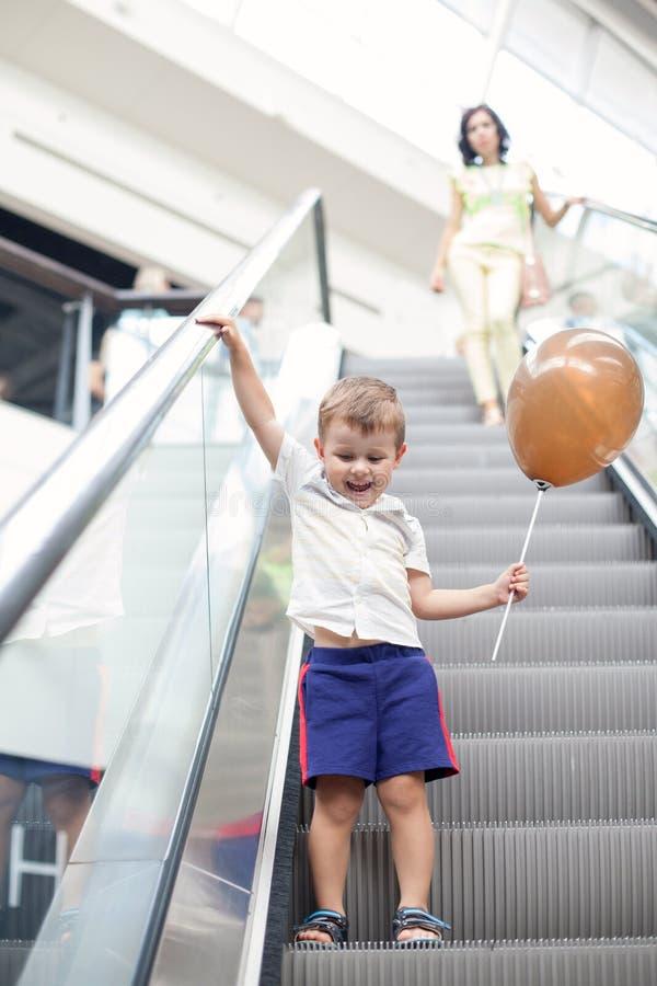 Gelukkig kind op roltrap in winkelcentrum Weinig jongen die bruine ballon houden stock foto's