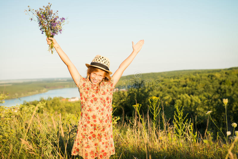 Gelukkig kind in openlucht in de heuvel Ontspannen meisje die wapens opheffen bij s royalty-vrije stock foto's