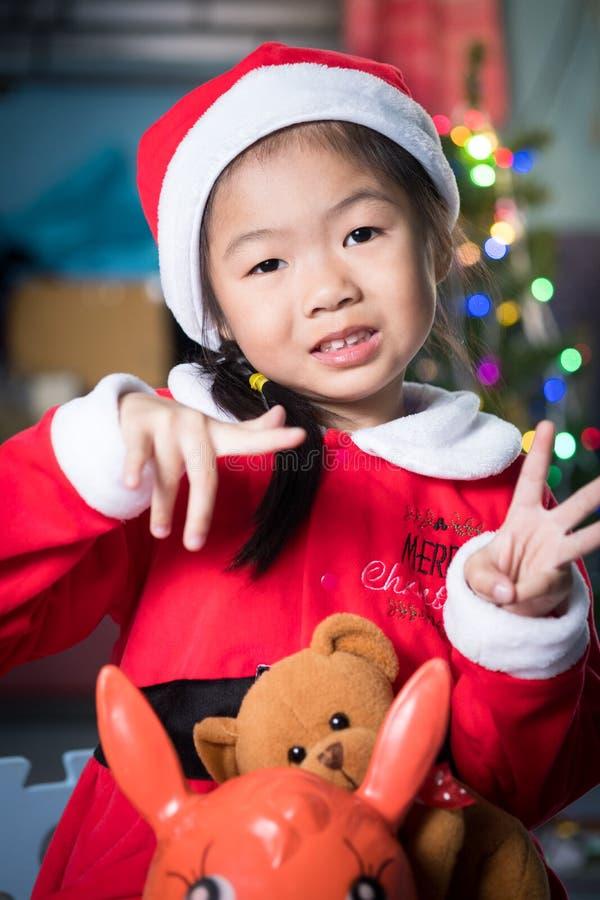 Gelukkig kind in santahoed met een gift dichtbij de Kerstboom, CH royalty-vrije stock afbeeldingen