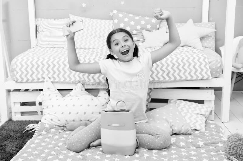 Gelukkig kindconcept Gelukkig meisjekind met giftzak Gelukkige kind geworden smartphone voor heden Gelukkige Verjaardag stock afbeeldingen