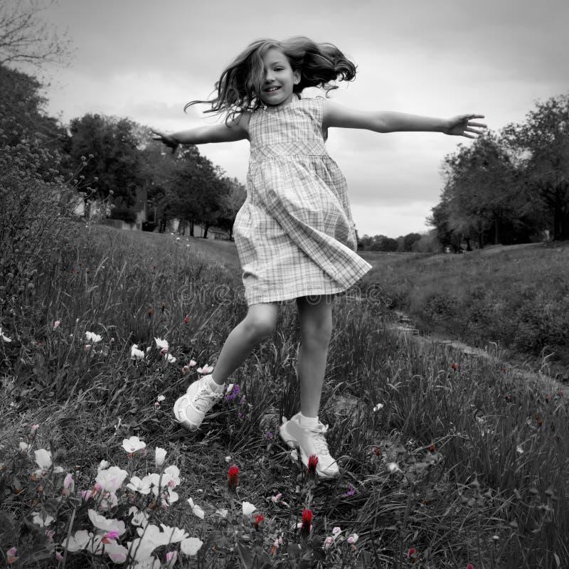 Gelukkig kinderenmeisje die op de bloemen van de de lentepapaver springen royalty-vrije stock fotografie