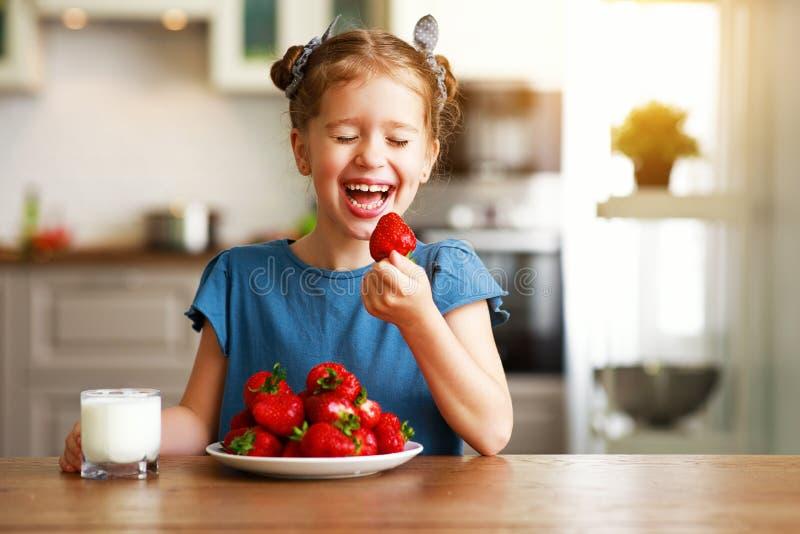 Gelukkig kindmeisje die aardbeien met melk eten stock afbeelding