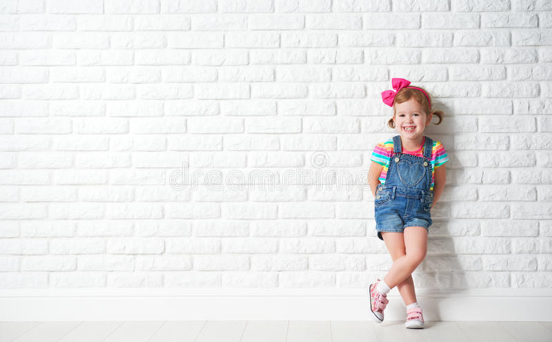 Gelukkig kindmeisje die bij lege bakstenen muur lachen stock afbeelding